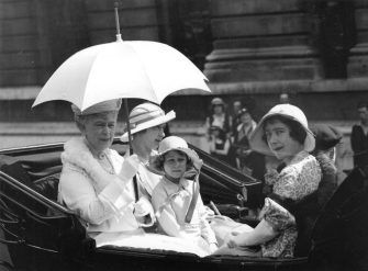 5th June 1933:  Queen Mary, Queen Consort to King George V, (1867 - 1953) (left), with her daughter Princess Mary, the Princess Royal beside her, and Elizabeth the Duchess of York (1900 - 2002, right) and grandaughter, Princess Elizabeth of York travelling in a carriage at a Trooping of the Colour ceremony at St. James' s Palace, London.  (Photo by Keystone/Getty Images)