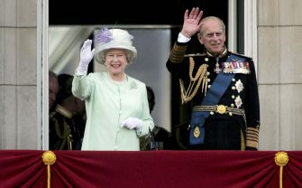 LONDON, UNITED KINGDOM - JULY 10:  HM Queen Elizabeth II, The Queen, and Prince Philip, Duke of Edinburgh, watch the flypast over The Mall of British and US World War II aircraft from the Buckingham Palace balcony on National Commemoration Day July 10, 2005 in London.  Poppies were dropped from the Lancaster Bomber of the Battle Of Britain Memorial Flight as part of the flypast.  (Photo by Daniel Berehulak/Getty Images)