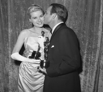 """(Original Caption) Actress Grace Kelly holding her Oscar after she was honored as the """"Best Actress"""" of 1954 at the 27th Academy Awards. She won the prize for her role in The Country Girl. Oscar-winner Kelly is kissed by Oscar winner Marlon Brando, he got an Oscar as the """"Best Actor"""" for his role in On The Waterfront."""