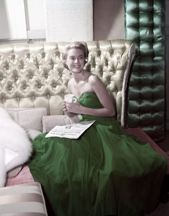 American actress Grace Kelly (1929 - 1982) wearing a green dress for St Patrick's Day, 1954. She is reading a copy of MGM's Studio News. (Photo by Gene Lester/Getty Images)