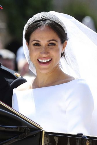 FILE - In this May 19, 2018, file photo, Meghan Markle leaves with Prince Harry after their wedding ceremony, at St. George's Chapel in Windsor Castle in Windsor, near London, England. With two blockbuster British royal weddings this year and an enduring fascination with the Brits, American brides craving a regal look with personal twists can find plenty of inspiration. (Gareth Fuller/pool photo via AP, File)