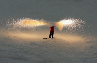 QUEENSTOWN, NEW ZEALAND - AUGUST 30:  Byron Wells of New Zealand skies down Coronet Peak while holding flares during the Closing Ceremony for the Winter Games NZ at Coronet Peak on August 30, 2009 in Queenstown, New Zealand.  (Photo by Phil Walter/Getty Images)