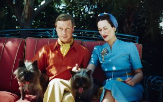 The Duke and Duchess of Windsor seated outdoors with two small dogs.