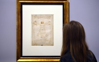 "A woman looks at the ""Vitruvian Man"" a drawing by Leonardo da Vinci, on August 2ç, 2013 in Venice. Fifty-two drawings by Renaissance genius Leonardo da Vinci are going on show in Venice from Thursday, including the famous but rarely-seen Vitruvian Man charting the ideal proportions of the human body. The show in the city's Galleria dell'Academia displays works from the museum's own archives as well as from the collections of the British Royal Family, the Ashmolean Museum, the British Museum and the Louvre. AFP PHOTO / GABRIEL BOUYS        (Photo credit should read GABRIEL BOUYS/AFP via Getty Images)"