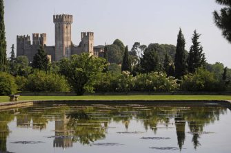 Water gardens of Sigurta Garden Park, the Scaliger Castle, 13th century, in the background, Valeggio sul Mincio, Veneto, Italy.