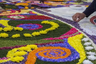 SPELLO, ITALY - JUNE 03:  People decorate the streets with flower petals during the Infiorata festival ahead of the religious procession of Corpus Domini on June 3, 2018 in Spello, Italy. The 'INFIORATA' event has became a true tribute to the Corpus Domini religious feast, which takes place on the ninth Sunday after Easter. Dating back to the seventeenth century, floral creations cover streets throughout the town of Spello in preparation to the passage of the Blessed Sacrament carried in procession by the bishop on Sunday morning.  (Photo by Tony Anna Mingardi/Awakening/Getty Images)