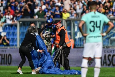Inter Milan's Italian defender Cristiano Biraghi (R) looks on as security staffers evacuate a parachutist (Rear C-L with helmet) that unexpectedly landed on the pitch during the first half of the Italian Serie A football match Sassuolo vs Inter Milan on October 20, 2019 at the Mapei stadium in Reggio-Emilia. (Photo by Miguel MEDINA / AFP) (Photo by MIGUEL MEDINA/AFP via Getty Images)
