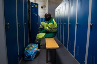 An employee of the Derichebourg waste management company operating for the Paris municipality, dons on his uniform in a locker room in La Courneuve on April 16, 2020, on the 31st day of a lockdown across France aimed at curbing the spread of the COVID-19 infection caused by the novel coronavirus. (Photo by JOEL SAGET / AFP) (Photo by JOEL SAGET/AFP via Getty Images)