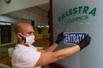 SALERNO, ITALY - MAY 23: Marco Rarità, Olimpica Gym Personal Trainer positions an entrance sign on the door on May 23, 2020 in Salerno, Italy. Restaurants, bars, cafes, hairdressers and other shops have reopened, subject to social distancing measures, after more than two months of a nationwide lockdown meant to curb the spread of Covid-19. (Photo by Francesco Pecoraro/Getty Images)