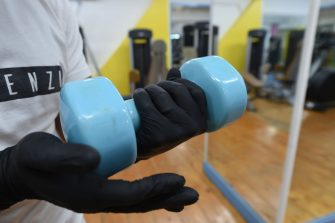SALERNO, ITALY - MAY 23: A person holds a gym weight while wearing gloves at the Olimpica Gym on May 23, 2020 in Salerno, Italy. Restaurants, bars, cafes, hairdressers and other shops have reopened, subject to social distancing measures, after more than two months of a nationwide lockdown meant to curb the spread of Covid-19. (Photo by Francesco Pecoraro/Getty Images)