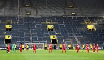 epa08445260 Players observe a minute of silence for the victims of the ongoing COVID-19 coronavirus pandemic before the German Bundesliga soccer match between Borussia Dortmund and FC Bayern Munich at Signal Iduna Park in Dortmund, Germany, 26 May 2020.  EPA/Federico Gambarini / POOL DFL regulations prohibit any use of photographs as image sequences and/or quasi-video.