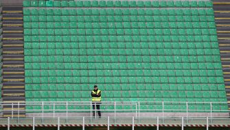 MILAN, ITALY - MARCH 08:  A steward looks on from an empty stand during the Serie A match between AC Milan and Genoa CFC which is being played in a closed stadium at Stadio Giuseppe Meazza on March 8, 2020 in Milan, Italy.  (Photo by Marco Luzzani/Getty Images)