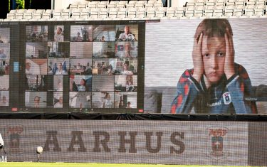 A young fan holds his head as fans are streamed live on to the screens on the sidelines during the 3F Super League football match between AGF and Randers FC at Ceres Park in Aarhus, Denmark, on May 28, 2020, as the season resumed following a two-month absence due to the novel coronavirus COVID-19 pandemic. (Photo by Henning Bagger / Ritzau Scanpix / AFP) / Denmark OUT (Photo by HENNING BAGGER/Ritzau Scanpix/AFP via Getty Images)