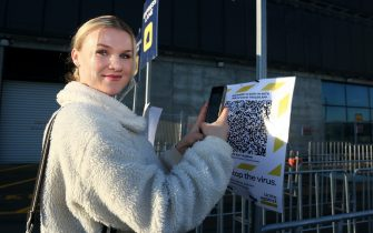 DUNEDIN, NEW ZEALAND - JUNE 13: A supporter signs in using the Covid-19 tracker app ahead of the Super Rugby match between the Highlanders and Chiefs on June 13, 2020 in Dunedin, New Zealand. (Photo by Dianne Manson/Getty Images)