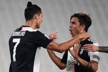 Juventus' Argentine forward Paulo Dybala (R) celebrates with Juventus' Portuguese forward Cristiano Ronaldo after opening the scoring during the Italian Serie A football match Juventus vs Lecce played on June 26, 2020 behind closed doors at the Juventus stadium in Turin, as the country eases its lockdown aimed at curbing the spread of the COVID-19 infection, caused by the novel coronavirus. (Photo by Miguel MEDINA / AFP) (Photo by MIGUEL MEDINA/AFP via Getty Images)