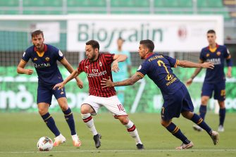 MILAN, ITALY - JUNE 28: AC Milan's Turkish midfielder Hakan Calhanoglu takes the ball past AS Roma's Italian midfielder Lorenzo Pellegrini as AS Roma's Italian midfielder Bryan Cristante looks on during the Serie A match between AC Milan and  AS Roma at Stadio Giuseppe Meazza on June 28, 2020 in Milan, Italy. (Photo by Jonathan Moscrop/Getty Images)