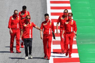 Ferrari's German driver Sebastian Vettel and his team inspect the track on July 2, 2020, on the eve of the first practice session at the Austrian Formula One Grand Prix in Spielberg, Austria. - Seven months after they last competed in earnest, the Formula One circus will push a post-lockdown re-set button to open the 2020 season in Austria on July 5. (Photo by JOE KLAMAR / AFP) (Photo by JOE KLAMAR/AFP via Getty Images)