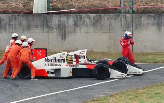 Ayrton Senna of Brazil is given a push from circuit marshals for a restart while his teammate and bitter rival Alain Prost of France leaves his car to abandon the race after the two collided in a chicane during the Japan Formula One Grand Prix in Suzuka 22 October 1989. Senna received the chequered flag but was later disqualified after being accused of receiving an illegal push from marshals and of taking a short cut through the chicane. AFP PHOTO TOSHIFUMI KITAMURA (Photo credit should read TOSHIFUMI KITAMURA/AFP via Getty Images)