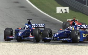 SPIELBERG, AUSTRIA:  French Prost-Peugeot driver Jean Alesi (L) and his teammate German Nick Heidfeld crashed during the Austrian Formula One Grand Prix on the racetrack in Speilberg, 16 July 2000.  (ELECTRONIC IMAGE) AFP PHOTO PPATRICK HERTZOG (Photo credit should read PATRICK HERTZOG/AFP via Getty Images)