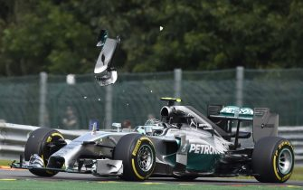 A pice of wing flys over Mercedes-AMG's German driver Nico Rosberg after a collision with teammate Mercedes-AMG's British driver Lewis Hamilton at the Spa-Francorchamps ciruit in Spa on August 24, 2014 during the Belgium Formula One Grand Prix.      AFP PHOTO / JOHN THYS        (Photo credit should read JOHN THYS/AFP via Getty Images)