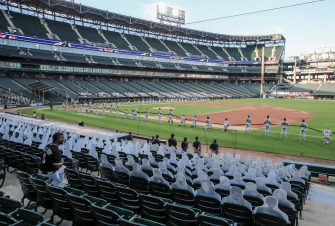 epa08565099 A member of the Chicago White Sox organization (L) kneels along with some of the players during the National Anthem before the start of the MLB baseball game between the Minnesota Twins and the Chicago White Sox at Guaranteed Rate Field in Chicago, Illinois, USA, 24 July 2020. Major League Baseball has started an abbreviated 2020 season playing in ballparks without fans.  EPA/TANNEN MAURY