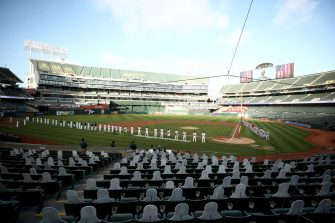OAKLAND, CALIFORNIA - JULY 24:  The Los Angeles Angels and the Oakland Athletics stand and kneel during the National Anthem before their opening day game at Oakland-Alameda County Coliseum on July 24, 2020 in Oakland, California. The 2020 season had been postponed since March due to the COVID-19 pandemic. (Photo by Ezra Shaw/Getty Images)