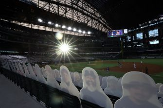 ARLINGTON, TEXAS - JULY 24:  Cardboard cut-out images of fans are seen as the sun sets in the third inning of play between the Colorado Rockies and the Texas Rangers on Opening Day at Globe Life Field on July 24, 2020 in Arlington, Texas.  The 2020 season had been postponed since March due to the COVID-19 pandemic.   (Photo by Ronald Martinez/Getty Images)