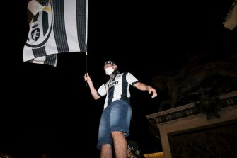 TURIN, ITALY - JULY 26: A Juventus FC fan wearing a protective mask celebrates the team's Serie A victory over UC Sampdoria on July 26, 2020 in Turin, Italy. Fans gathered to celebrate the team's ninth consecutive Scudetto. (Photo by Stefano Guidi/Getty Images)