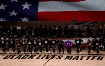 LAKE BUENA VISTA, FLORIDA - JULY 30: The Los Angeles Lakers and the LA Clippers wear Black Lives Matter Shirt and kneel during the national anthem prior to the game against the LA Clippers at The Arena at ESPN Wide World Of Sports Complex on July 30, 2020 in Lake Buena Vista, Florida. NOTE TO USER: User expressly acknowledges and agrees that, by downloading and or using this photograph, User is consenting to the terms and conditions of the Getty Images License Agreement. (Photo by Mike Ehrmann/Getty Images)