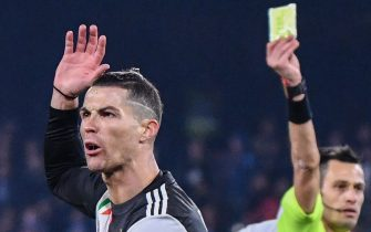 Juventus' Portuguese forward Cristiano Ronaldo (L) reacts as he receives a yellow card from Italian referee Maurizio Mariani (R) during the Italian Serie A football match Napoli vs Juventus on January 26, 2020 at the San Paolo stadium in Naples. (Photo by Alberto PIZZOLI / AFP) (Photo by ALBERTO PIZZOLI/AFP via Getty Images)