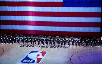 LAKE BUENA VISTA, FL - JULY 31: Players kneel behind a Black Lives Matter court decal before the start of a game between the Brooklyn Nets and the Orlando Magic on July 31, 2020 at The HP Field House at ESPN Wide World Of Sports Complex in Lake Buena Vista, Florida. NOTE TO USER: User expressly acknowledges and agrees that, by downloading and/or using this Photograph, user is consenting to the terms and conditions of the Getty Images License Agreement. (Photo by Ashley Landis - Pool/Getty Images)