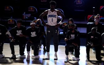 LAKE BUENA VISTA, FL - JULY 31: Jonathan Isaac #1 of the Orlando Magic stands as others kneel before the start of a game between the Brooklyn Nets and the Orlando Magic on July 31, 2020 at The HP Field House at ESPN Wide World Of Sports Complex in Lake Buena Vista, Florida. NOTE TO USER: User expressly acknowledges and agrees that, by downloading and/or using this Photograph, user is consenting to the terms and conditions of the Getty Images License Agreement. (Photo by Ashley Landis - Pool/Getty Images)