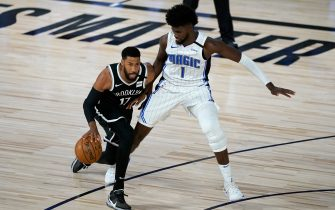LAKE BUENA VISTA, FL - JULY 31: Garrett Temple #17 of the Brooklyn Nets dribbles past Jonathan Isaac #1 during the first half on July 31, 2020 at The HP Field House at ESPN Wide World Of Sports Complex in Lake Buena Vista, Florida. NOTE TO USER: User expressly acknowledges and agrees that, by downloading and/or using this Photograph, user is consenting to the terms and conditions of the Getty Images License Agreement. (Photo by Ashley Landis - Pool/Getty Images)