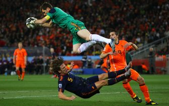 JOHANNESBURG, SOUTH AFRICA - JULY 11:  Iker Casillas of Spain catches the ball ahead of Robin Van Persie of the Netherlands as Carles Puyol of Spain falls to the ground during the 2010 FIFA World Cup South Africa Final match between Netherlands and Spain at Soccer City Stadium on July 11, 2010 in Johannesburg, South Africa.  (Photo by Lars Baron/Getty Images)