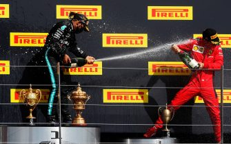 NORTHAMPTON, ENGLAND - AUGUST 02: Race winner Lewis Hamilton of Great Britain and Mercedes GP (L) and third-placed Charles Leclerc of Monaco and Ferrari (R) celebrate on the podium during the F1 Grand Prix of Great Britain at Silverstone on August 02, 2020 in Northampton, England. (Photo by Frank Augstein/Pool via Getty Images)