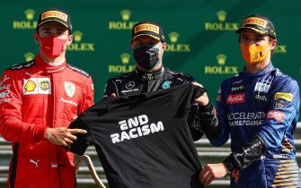 """(L-R) Ferrari's Monegasque driver Charles Leclerc, Mercedes' Finnish driver Valtteri Bottas and McLaren's British driver Lando Norris pose with a """"End Racism"""" t-shirt on the podium after the Austrian Formula One Grand Prix race on July 5, 2020 in Spielberg, Austria. (Photo by Mark Thompson / POOL / AFP) (Photo by MARK THOMPSON/POOL/AFP via Getty Images)"""