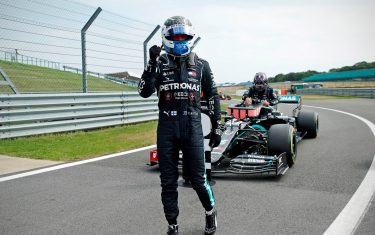 Mercedes' Finnish driver Valtteri Bottas celebrates in the pit lane after taking pole position as Mercedes' British driver Lewis Hamilton (back) gets out of his car during the qualifying session of the F1 70th Anniversary Grand Prix at Silverstone on August 8, 2020 in Northampton. - This weekend's race will commemorate the 70th anniversary of the inaugural world championship race, held at Silverstone in 1950. (Photo by ANDREW BOYERS / POOL / AFP) (Photo by ANDREW BOYERS/POOL/AFP via Getty Images)