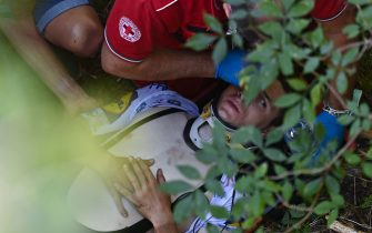 Deceuninck - Quick Step Belgium rider Remco Evenepoel is helped by staff member and medical staff as he lies down after crashed during the 114th edition of the giro di Lombardia (Tour of Lombardy),  a 231 km cycling race from Bergamo to Como on August 15, 2020. (Photo by Marco BERTORELLO / AFP) (Photo by MARCO BERTORELLO/AFP via Getty Images)