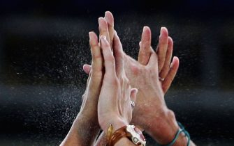 ATHENS - AUGUST 17:  The hands of Kerri Walsh and Misty May of the USA come together in celebration during the women's preliminary match on August 17, 2004 during the Athens 2004 Summer Olympic Games at the Olympic Beach Volleyball Centre at the Faliro Coastal Zone Complex in Athens, Greece. (Photo by Ian Waldie/Getty Images)