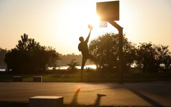 DUSSELDORF, GERMANY - APRIL 26: A teenager drives to the basketball hoop on a public court near the river Rhine at sunset during the novel coronavirus crisis on April 26, 2020 in Dusseldorf, Germany. Germany is taking its first steps to ease restrictions on public life that had been imposed weeks ago in order to stem the spread of the coronavirus. Shops across the country are reopening, factory assembly lines are restarting and high schools are holding final exams. Health leaders are monitoring the process carefully for any resurgence of coronavirus infections. The number of infections nationwide is still rising, though so far at a declining rate. (Photo by Andreas Rentz/Getty Images)