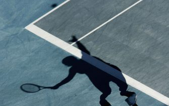 ATHENS - AUGUST 16:  (THIS PHOTO HAS BEEN ROTATED 180 DEGREES FOR AESTHETIC PURPOSES) The shadow of Amelie Mauresmo of France is seen on the court as she serves to Conchita Martinez of Spain during their women's singles tennis match on August 16, 2004 during the Athens 2004 Summer Olympic Games at the Olympic Sports Complex Tennis Centre in Athens, Greece. (Photo by Robert Laberge/Getty Images)