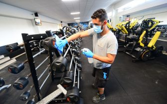 """TOPSHOT - A worker disinfects barbells at the """"Body Staff Gym"""" fitness centre on June 1, 2020, in Artigues-pres-Bordeaux, southwestern France, as part of safety measures on the eve of the reopening of the gym, as France eases lockdown measures taken to curb the spread of the COVID-19 pandemic, caused by the novel coronavirus. - France preapres for the long-awaited nationwide reopening of bars, restaurants and cafes from June 2, albeit with restrictions, and lifted limitations on domestic travel in time for the summer holidays. In zones labeled """"green"""" gyms, swimming pools and fitness centres can also reopen. (Photo by MEHDI FEDOUACH / AFP) (Photo by MEHDI FEDOUACH/AFP via Getty Images)"""