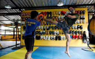 epa08464277 Muay Thai boxing enthusiast, Arthur Simon (R) from France and Thai trainer Viroj Wanram (L) wear face masks to prevent the COVID-19 coronavirus pandemic during Muay Thai Boxing practice class at Cheeks Thai Boxing Club in Bangkok, Thailand, 04 June 2020. Thailand easing the third stage of lockdown to restart its business and activity after the slowdown of COVID-19 coronavirus as the number of infections continue to drop.  EPA/RUNGROJ YONGRIT