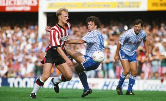 SOUTHAMPTON, UNITED KINGDOM - SEPTEMBER 14: Southampton centre forward Iain Dowie (l) beats Mark Hughes to the ball as Bryan Robson (r) looks on during a League Division One match between Southampton and Manchester United at The Dell on September 14, 1991 in Southampton, England.  (Photo by Steve Morton/Allsport/Getty Images)