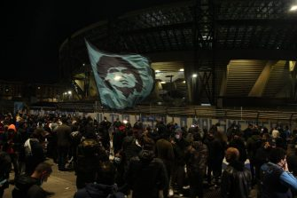 People gather at the main entrance of the San Paolo stadium in Naples on November 25, 2020 waving a flag at the effigy of Argentinian football legend Diego Maradona, to mourn after the annoucement's of Maradona's death. - Argentine football legend Diego Maradona has died at the age of 60, his spokesman announced November 25, 2020. (Photo by CARLO HERMANN / AFP) (Photo by CARLO HERMANN/AFP via Getty Images)