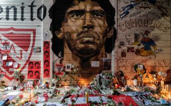 epa08842744 Floral offerings, flags, candles and letters adorn a mural with the image of Diego Armando Maradona as an altar, at the Club Argentinos Juniors Stadium, in Buenos Aires, Argentina, 25 November 2020. Diego Maradona died on 25 November 2020 following a heart attack, aged 60.  EPA/Juan Ignacio Roncoroni