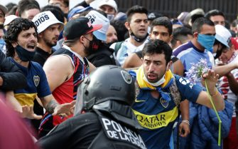 Diego Maradona's fans argue with police to enter the Government House to pay tribute to late football legend Diego Armando Maradona in Buenos Aires, on November 26, 2020. - Diego Maradona's coffin arrived at the presidential palace in Buenos Aires for a period of lying in state, TV reports showed, following the death of the Argentine football legend aged 60 on November 25. Hundreds of people were already lining up to pay their respects to Maradona, who died while recovering from a brain operation, the images from sports channels TyC and ESPN showed. (Photo by ALEJANDRO PAGNI / AFP) (Photo by ALEJANDRO PAGNI/AFP via Getty Images)