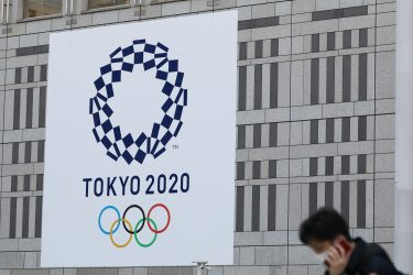 (200330) -- TOKYO, March 30, 2020 (Xinhua) -- A man wearing protective face masks walk past the logo of the Tokyo 2020 Olympic Games displayed on a wall of The Tokyo Metropolitan Government Building in Tokyo, Japan, March 25, 2020. The Tokyo Olympic Games has been rescheduled to July 23 to August 8, 2021, organizers of the Tokyo 2020 Olympic and Paralympic Games announced on Monday. (Xinhua/Du Xiaoyi) - Du Xiaoyi -//CHINENOUVELLE_1822028/2003301834/Credit:CHINE NOUVELLE/SIPA/2003301838 (Tokyo - 2020-03-25, CHINE NOUVELLE/SIPA / IPA) p.s. la foto e' utilizzabile nel rispetto del contesto in cui e' stata scattata, e senza intento diffamatorio del decoro delle persone rappresentate