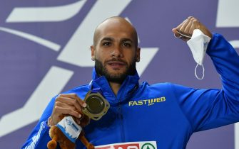 epa09058735 Gold medalist Lamont Marcell Jacobs of Italy  poses for a photo during the medal ceremony of the men's 60m competition at the 36th European Athletics Indoor Championships in Torun, north-central Poland, 07 March 2021.  EPA/ADAM WARZAWA POLAND OUT