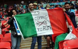 Tifose e tifosi italiani allo stadio di Wembley con una bandiera tricolore e uno slogan durante Euro 2020